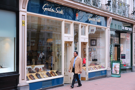 shoe store: BIRMINGHAM, UK - APRIL 19, 2013: Person walks by Gordon Scott shoe store in Birmingham, UK. Gordon Scott is a brand of Jones Bootmaker (100 locations in the UK), company founded in 1857.