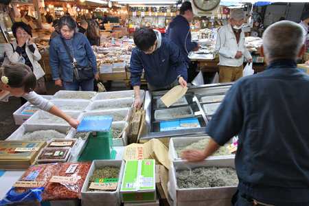 TOKYO, JAPAN - MAY 11, 2012: People visit famous Tsukiji Fish Market in Tokyo. It is the biggest wholesale fish and seafood market in the world.