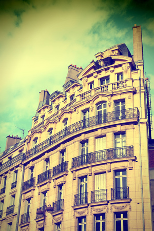 cross processed: Paris, France - typical old apartment building. Windows and balconies. Cross processed colors style - filtered tone retro image.