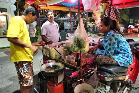 HUA HIN, THAILAND - DECEMBER 13, 2013: Person cooks typical street food in Thailand. 26.7 million people visited Thailand in 2013, some of them to enjoy Thai cuisine.