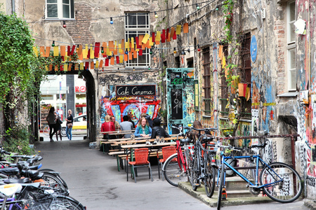 BERLIN, GERMANY - AUGUST 27, 2014: People visit old Hackesche Hofe in Berlin. The art nouveau architecture complex dates back to 1906 and part of it is covered in notable urban art.