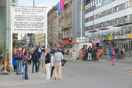 cold war: BERLIN, GERMANY - AUGUST 26, 2014: People visit famous Checkpoint Charlie in Berlin. During the Cold War it was the best known crossing of Berlin Wall.