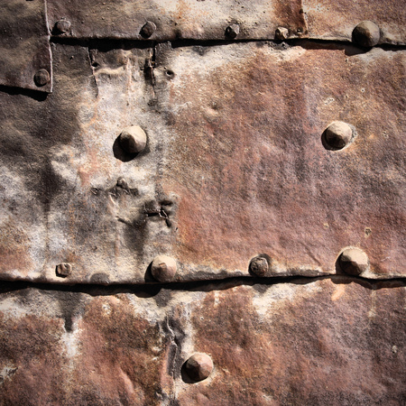 bolted: Vintage rusty iron background - metal plates with bolts. Grunge texture. Square composition. Stock Photo