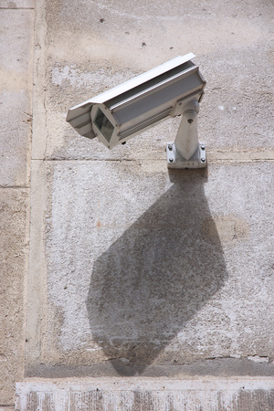 Surveillance camera in the city - electronic security technology. photo