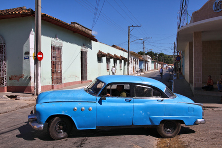 capita: TRINIDAD, CUBA - FEBRUARY 6, 2011: Person drives old car in Trinidad. Cuba has one of the lowest car-per-capita rates (38 per 1000 people in 2008).