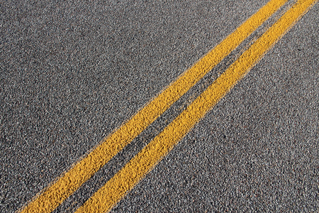 Asphalt concrete roadway pavement surface. Grey background with yellow line. Stock Photo