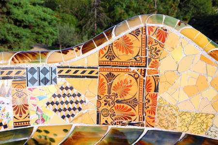 BARCELONA, SPAIN - NOVEMBER 6, 2012: Mosaics in Park Guell in Barcelona, Spain. The landmark was built in 1900-14 and is part of the UNESCO World Heritage Site Works of Antoni Gaudi.