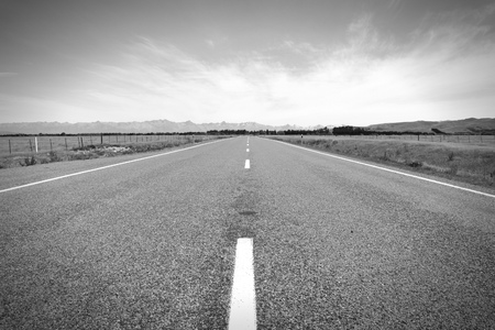 New Zealand. Straight road. Plains and mountains in Canterbury region. Black and white tone - retro monochrome color style. Stock Photo
