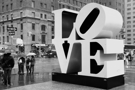 NEW YORK, USA - JUNE 7, 2013: People walk past Love sculpture in rain in New York City. The famous monument by Robert Indiana is located on 6th Avenue.