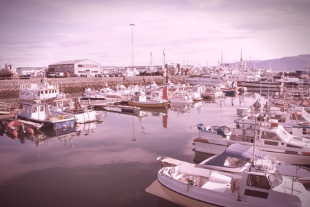 motorboats: Reykjavik harbor. Motorboats, yachts and small fishing ships. Cross processed color tone - retro filtered style.
