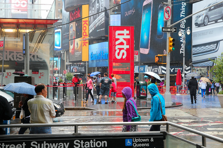 NEW YORK, USA - JUNE 10, 2013: People walk in rain in Times Square, NY. Times Square is one of most recognized places in the world. More than 300,000 people pass through Times Square daily.