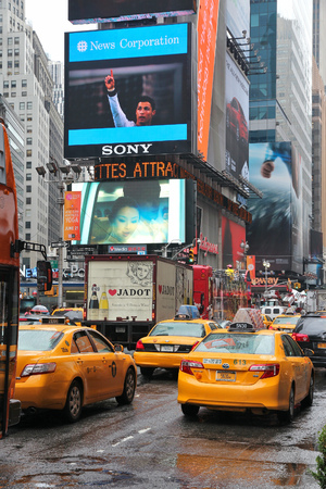 NEW YORK, USA - JUNE 10, 2013: Taxis drive in rain in Times Square, NY. Times Square is one of most recognized places in the world. More than 300,000 people pass through Times Square daily.