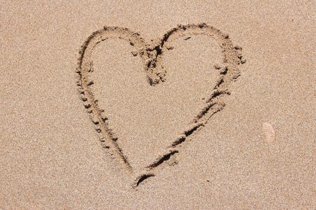 sandy: Finger drawing on a sandy beach - heart shape, symbol of love.