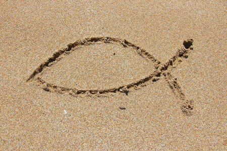 Christianity symbol - religious shape drawn in sand. Catholicism fish - ichthus.