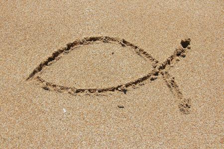 catholicism: Christianity symbol - religious shape drawn in sand. Catholicism fish - ichthus.