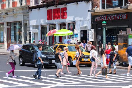 cross street: NEW YORK, USA - JULY 5, 2013: People cross Broadway in SoHo district, New York. Almost 19 million people live in New York City metropolitan area.