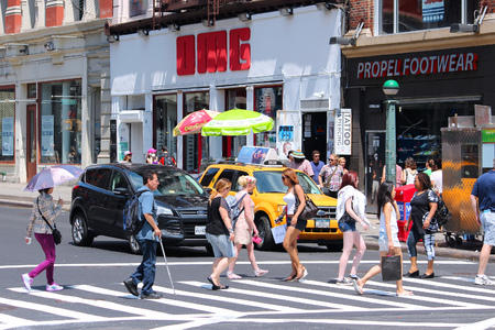 NEW YORK, USA - JULY 5, 2013: People cross Broadway in SoHo district, New York. Almost 19 million people live in New York City metropolitan area.
