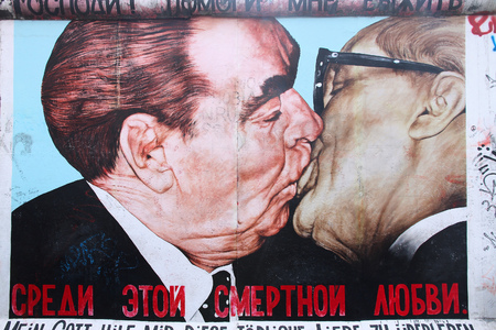 BERLIN, GERMANY - AUGUST 26, 2014: Urban art of East Side Gallery seen from public street in Berlin. Part of former Berlin Wall is covered in art by more than 100 artists since 1990. 新闻类图片