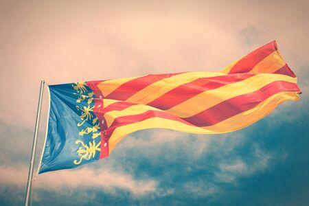 autonomic: Bandiera della Comunidad Valenciana, regione della Spagna. Spostamento nel vento. Attraversare tono di colore processato - immagine stile retr� filtrata.