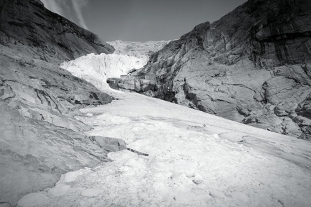 jostedalsbreen: Norway, Jostedalsbreen National Park. Famous  Briksdalsbreen glacier in Briksdalen valley. Black and white tone - retro monochrome color style.