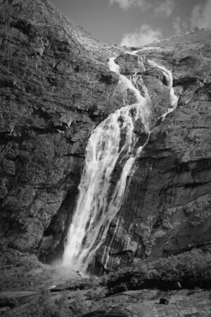 jostedalsbreen: Norway, Jostedalsbreen National Park. Waterfall originating from Jostedalsbreen glacier, falling into Briksdalen valley. Black and white tone - retro monochrome color style.