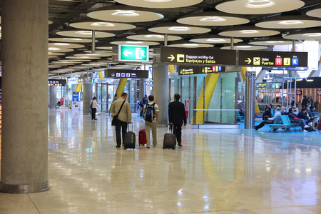 barajas: MADRID, SPAIN - OCTOBER 20, 2014: People hurry at Terminal 4 of Madrid Barajas Airport. The famous Terminal 4 was designed by Antonio Lamela and Richard Rogers.