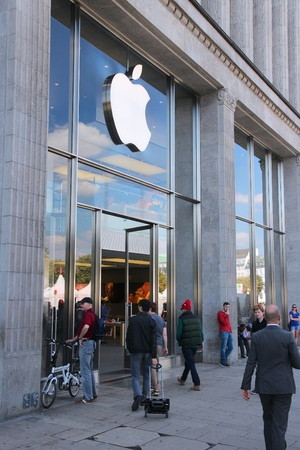 traded: HAMBURG, GERMANY - AUGUST 28, 2014: People visit Apple Store in Hamburg. Since November 2014 Apple Inc is the largest publicly traded company in the world by market capitalization.