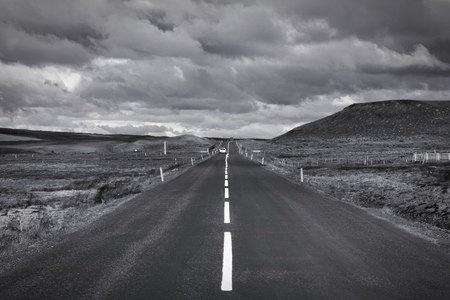 Straight road in Iceland. Volcanic area of Krafla. Vanishing point. Black and white tone - retro monochrome color style. Stock Photo