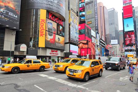 뉴욕, 미국 -2010 년 7 월 3 일 - 2013 년 : 택시는 뉴욕의 타임스 스퀘어 (Times Square)를 따라 드라이브. 타임스 스퀘어 (Times Square)는 미국에서 가장 인정 랜드