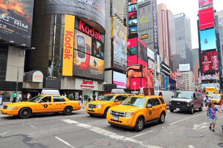 new york city times square: NEW YORK, USA - JULY 3, 2013: Taxis drive along Times Square in New York. Times Square is one of most recognized landmarks in the USA. More than 300,000 people visit Times Square every day.