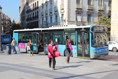 emt: MADRID, SPAIN - OCTOBER 22, 2012: People exit city bus in Madrid. EMT is Madrids main bus operator. It uses fleet of more than 2000 buses and serves about 450 million rides annually (2011).