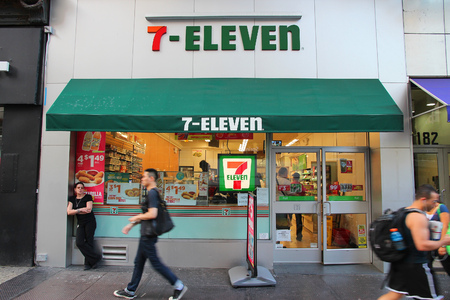 convenient store: NEW YORK, USA - JULY 3, 2013: People walk past 7-Eleven convenience store in New York. 7-Eleven is worlds largest operator, franchisor and licensor of convenience stores, with more than 46,000 shops.