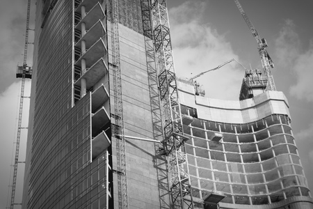 highriser: Skyscraper construction in Milan, Italy. Office building development. Black and white tone.