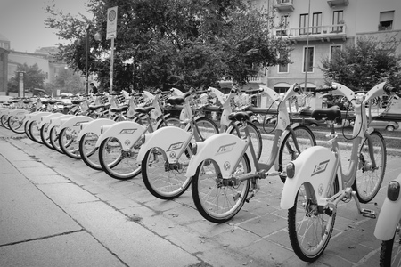 shared sharing: MILAN, ITALY - OCTOBER 7, 2010: City bicycles in Milan, Italy. With 1000 bicycles and 100 stations, BikeMi is among largest bike sharing systems worldwide. Editorial
