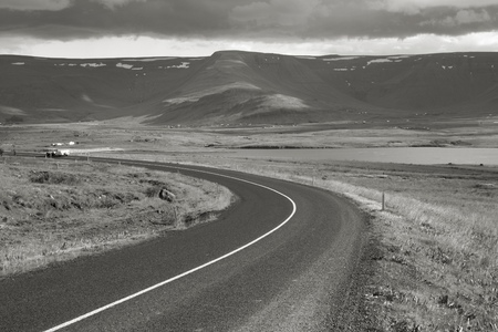 fiord: Road curve next to Hvalfjordur fiord in Iceland. Black and white monochrome tone. Stock Photo