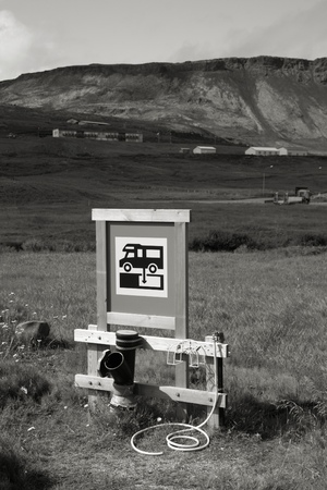 rv: RV camping sewage dump station at a campground in Iceland. Focus on the sign. Black and white monochrome tone.