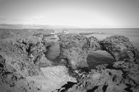 rock arch: Natural rock arch in Arnarstapi, Snafellsnes peninsula, Iceland. Black and white tone. Stock Photo
