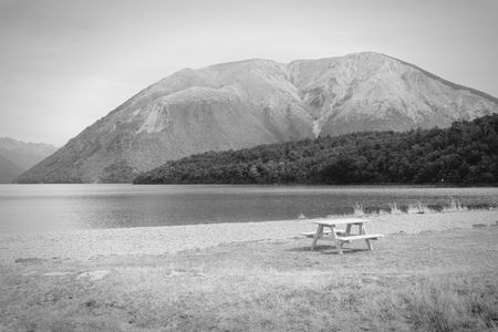 australasia: New Zealand. Nelson Lakes National Park - empty bench. Black and white tone - retro monochrome color style.
