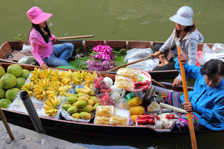 saduak: RATCHABURI, THAILAND - DECEMBER 24, 2013: Vendors sell food at Damnoen Saduak floating market. Damnoen Saduak is the most popular floating market in Thailand.