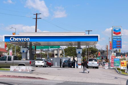 fill up: LOS ANGELES, USA - APRIL 5, 2014: People fill up their cars at Chevron gas station in Los Angeles. Chevron is a multinational energy corporation it employs 64,600 people (2013).