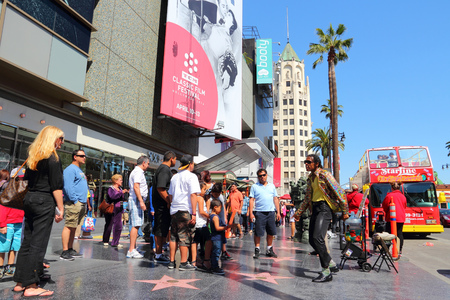 fame: LOS ANGELES, USA - APRIL 5, 2014: People visit famous Walk of Fame in Hollywood. Hollywood Walk of Fame features more than 2,500 stars with inscribed celebrity names. Editorial