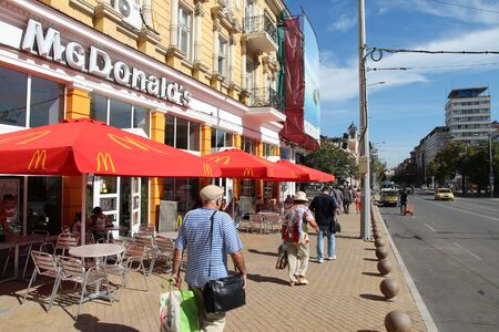 mcdonalds: SOFIA, BULGARIA - AUGUST 17, 2012: People walk by McDonalds restaurant in Sofia, Bulgaria. McDonalds is the 2nd most successful restaurant franchise in the world with 33,000 locations.