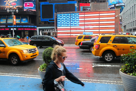 new york city times square: NEW YORK, USA - JUNE 10, 2013: People walk in rain in Times Square, New York City. Times Square has over 39 million annual visitors. It is an important landmark of Midtown Manhattan. Editorial