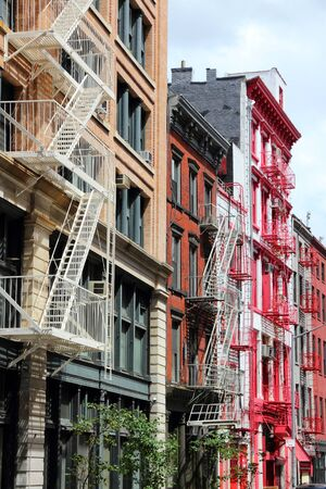 New York City, United States - old residential buildings in Soho district. Colorful fire escape stairs. Stock Photo