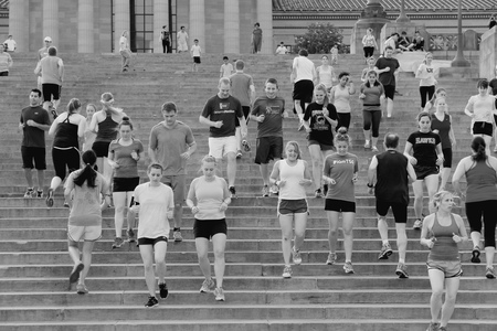 run down: PHILADELPHIA, USA - JUNE 11, 2013: People run down famous Rocky Steps in Philadelphia. The steps were made famous by the film Rocky and are known among runners of the world.