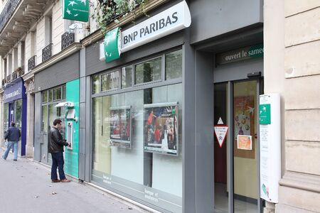 bank branch: PARIS, FRANCE - JULY 23, 2011: Person visits BNP Paribas Bank branch in Paris, France. Formed through merger in 2000, the bank is currently largest worldwide by assets ($2.68 trillion USD). Editorial