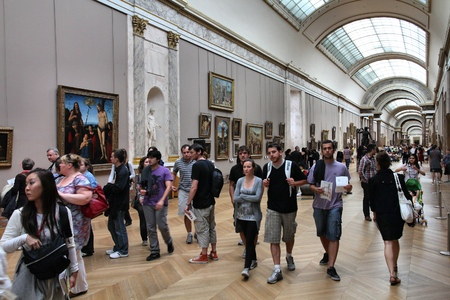 museum visit: PARIS, FRANCE - JULY 22, 11: Tourists visit Louvre Museum in Paris, France. With 8.5m annual visitors, Louvre is consistently the most visited museum worldwide.
