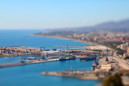 tilt view: Malaga in Andalusia, Spain. Aerial view of port and the city. Tilt shift style focus with defocused background.