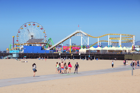 monica: SANTA MONICA, UNITED STATES - APRIL 6, 2014: People visit beach in Santa Monica, California. As of 2012 more than 7 million visitors from outside of LA county visited Santa Monica annually.