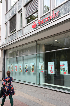 bank branch: BERLIN, GERMANY - AUGUST 27, 2014: People walk by Santander Bank branch in Berlin. Santander Group was ranked 43rd largest company in the world by Forbes in 2013. Editorial